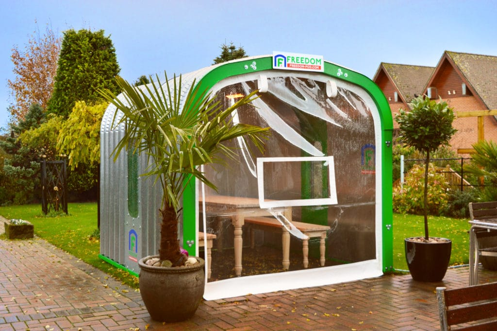 Freedom Pod Commercial Dining Pod on an outdoor terrace setting with bespoke table and bench set and wall with serving hatch